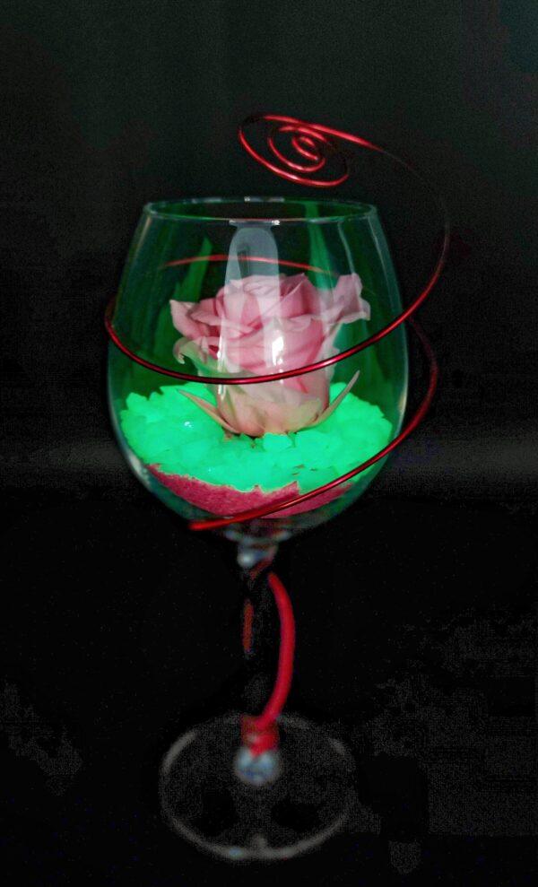 Rosa rosa preservada en la copa de cristal. La piedra que adornada la rosa se ilumina en oscuridad.