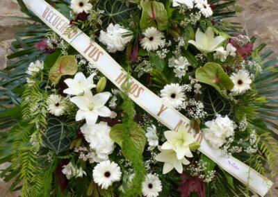 Corona blanca con anturium, gerberas, lilium, hotencias.